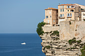 The Citadel and old town of Bonifacio perched on rugged cliffs with boat in the Mediterranean sea, Bonifacio, Corsica, France, Mediterranean, Europe