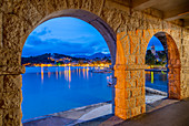 View of town and Crkva Sv. Nikole church through arches at dusk, Cavtat on the Adriatic Sea, Cavtat, Dubrovnik Riviera, Croatia, Europe