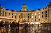 Christmas market on Michaelerplatz with Hofburg Palace at dusk, Vienna, Austria, Europe