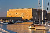 View across the Venetian Harbour, sunset, the Koules Fortress reflected in water, Iraklio (Heraklion), Crete, Greek Islands, Greece, Europe