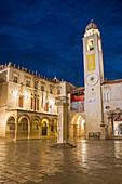 View across marble-paved Luza Square to the Sponza Palace and clock tower, dusk, Dubrovnik, Dubrovnik-Neretva, Dalmatia, Croatia, Europe