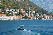 Small boat heading towards the waterfront across the Bay of Kotor, Perast, Kotor, UNESCO World Heritage Site, Montenegro, Europe