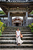 Japanese woman sitting on steps outside a Buddhist temple.