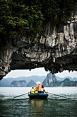Rear view of man wearing straw hat transporting small group of people on a boat, rowing underneath natural rock arch.
