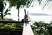 """Close up of a """"Tom Yum"""" cocktail with coconut-infused liquour standing a balustrade of balcony."""