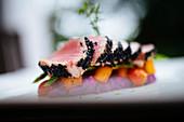 Close up of sesame crusted tuna on a plate.