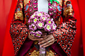 Close up of young Vietnamese bride wearing a colourful robe, holding a bouquet of lotus flowers.