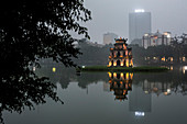 Exterior of illuminated temple reflected in a lake at dusk, skyscraper in the distance.