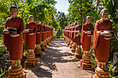 Row of Buddhist monk statues with red robes and alms bowls in the gardens of the Buddhist Temple at Siem Reap