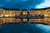 France, Gironde, Bordeaux, area listed as World Heritage by UNESCO, Bourse Place, La Lune harbour, Night view of a tram passing a historic building and their reflections on an esplanade water