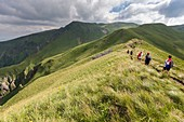 France, Puy de Dome, Chambon sur Lac, regional Natural reserve of the volcanoes of Auvergne, massif of Sancy, the nature reserve of the Valley of Chaudefour, walkers on the GR4, the path of the crests of the Volcanic hill of Cacadogne