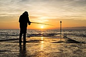 France, Finistere, Fouesnant, Pointe de Mousterlin, Fisherman on the pier at nightfall