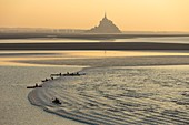 France, Manche, Mont Saint Michel bay, listed as World Heritage by UNESCO, a kayakists riding the Mascaret wave during fall high tides and Tombelaine islet in the background