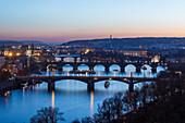 Dusk lights up the historical bridges and buildings reflected on Vltava River, Prague, Czech Republic, Europe