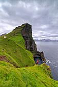 Hiker on cliffs looking to Kallur Lighthouse, Kalsoy Island, Faroe Islands, Denmark, Europe