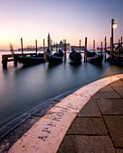 Langzeitbelichtung von Gondeln durch San Giorgio Maggiore bei Sonnenuntergang in Venedig, Italien, Europa