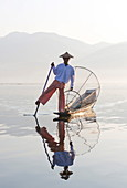 Intha 'leg rowing' fishermen on Inle Lake who row traditional wooden boats using their leg and fish using nets stretched over conical bamboo frames, Inle Lake, Myanmar (Burma), Southeast Asia