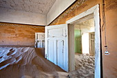 Interior of building slowly being consumed by the sands of the Namib Desert in the abandoned former German diamond mining town of Kolmanskop, Forbidden Diamond Area near Luderitz, Namibia, Africa