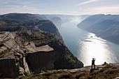 Mann fotografiert den Fjord, Preikestolen (Kanzelfelsen), Lysefjord, Norwegen, Skandinavien, Europa