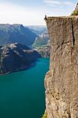 Mann sitzt auf Preikestolen (Kanzelfelsen) über dem Fjord, Lysefjord, Norwegen, Skandinavien, Europa