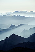 Mountains silhouetted at sunrise, view from Pico de Aneto, at 3404m the highest peak in the Pyrenees, Spain, Europe