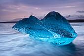 An den schwarzen Sand von Breidamerkursandur gespülter, durchscheinender, blauer Eisberg in der Nähe der Gletscherlagune von Jokulsarlon, Ostisland, Polarregionen