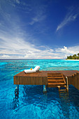 Sonnenliege und Steg in der blauen Lagune auf tropischer Insel, Malediven, Indischer Ozean, Asien
