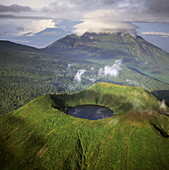 Aerial view of Mount Visoke (Mount Bisoke), an extinct volcano straddling the border of Rwanda and Democratic Republic of the Congo (DRC) showing crater lake, with Mount Mikeno in background, Virunga Volcanoes, Great Rift Valley, Africa