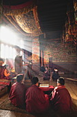 Junge Mönche nehmen an einer privaten Segenszeremonie teil im Morgengrauen im Ura-Tempel, Ura-Dorf, Bumthang-Tal, Bhutan, Asien