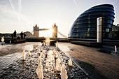 Sunrise behind Tower Bridge and The Mayor's Building (City Hall), London, England, United Kingdom, Europe