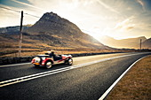 Open top classic sports car driving through Snowdonia, Wales, United Kingdom, Europe