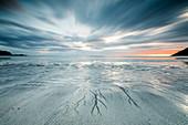 Midnight sun and clouds frame the sandy beach of Skagsanden, Flakstad, Nordland county, Lofoten Islands, Norway, Scandinavia, Europe