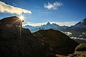 Wanderer gehen zur Berghütte am Lac de Cheserys mit der gerade aufgehenden Sonne, Chamonix, Haute Savoie, Französische Alpen, Frankreich, Europa