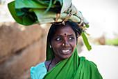 Eine Frau trägt aufgerollte Bananenblätter, die zum Einwickeln von Lebensmitteln verwendet werden, Karnataka, Indien, Asien