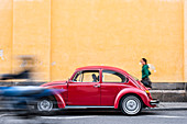 A woman walking past a red VW Beetle in the colourful streets of Popayan, Colombia, South America