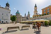 Blick auf Radfahrer und Salzburger Dom am Residenzplatz, Salzburg, Österreich, Europa