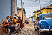 Elderly Cubans playing music on the street, American classic car, Trinidad, Sancti Spiritus Province, Cuba, West Indies, Caribbean, Central America