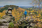 Man stands on rock tower and looks to the Gohrisch, Papststein, Elbe Sandstone Mountains, Saxon Switzerland National Park, Saxon Switzerland, Saxony, Germany