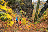 Man and woman hiking through autumn forest in the Elbe Sandstone Mountains, fire view, Elbe Sandstone Mountains, Saxon Switzerland National Park, Saxon Switzerland, Saxony, Germany