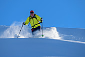 Man on ski tour starts through powder snow, Regenfeldjoch, Kitzbüheler Alpen, Tyrol, Austria