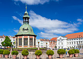 "Marktplatz (market square) in the centrum of Wismar, ""Wasserkunst"" historic ornate structure on the site of a 16th-century water fountain designed by Philipp Brandin; on the right Town Hall, Wismar stadt, Mecklenburg–Vorpommern, Germany."
