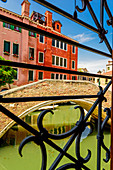 View through window grille on canal, Venice, Italy