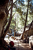 Children run on a hiking trail past rocks in Yosemite Park. California, United States.