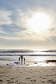 Father with young children on Santa Barbara beach. California, United States.