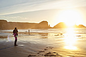 Father with child at sunset on Big Sur beach. California, United States