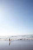 Child runs with the waves on Big Sur beach. California, United States