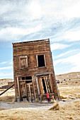 Child looks through a window into a skewed house in the ghost town of Bodie. Eastern Sierra, California, United States.