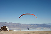 Paraglider takes off in a blue sky in front of the White Mountains. Walts Point at Lone Pine, California, USA.