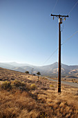 Electricity pylon on a road through reddish steppe grass. California, United States.