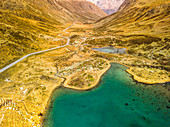 Turquoise shimmering mountain lake in a barren, yellow, golden pass landscape on the Julier Pass, Graubünden, Switzerland, Europe